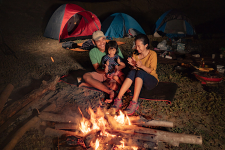 Happy family at camping with campfire