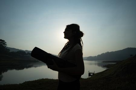 Silhouette of woman carrying mattress Banco de Imagens