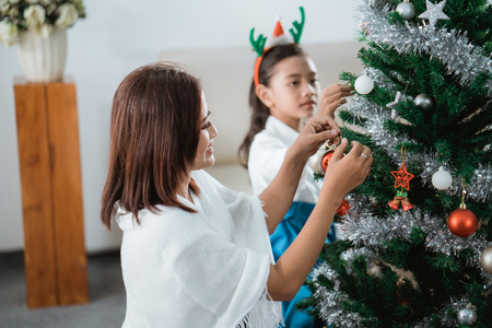 mom and daughter decorating christmas tree Stock Photo