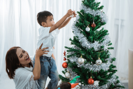 mother and son decorating christmas tree Standard-Bild