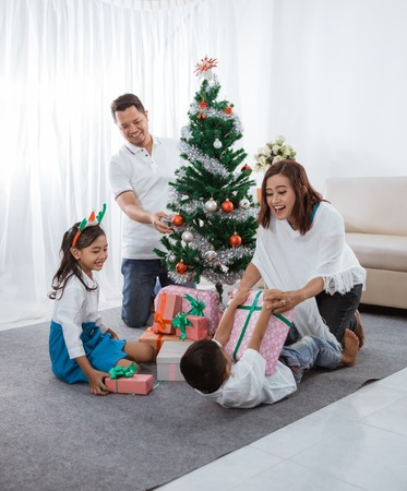 asian family decorate christmas tree
