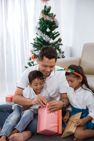 family try to open their christmas gift together Stock Photo