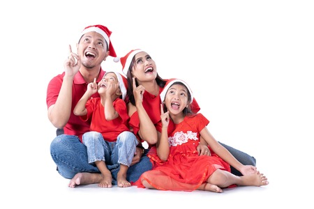 Christmas family pointing up to copy space
