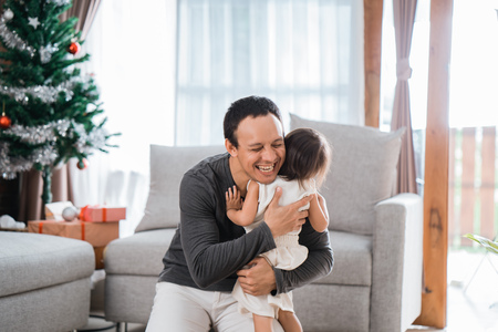 portrait of hugging father to daughter in living room