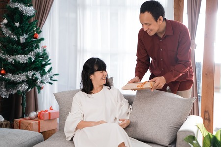 lovely husband surprising his wife with gift