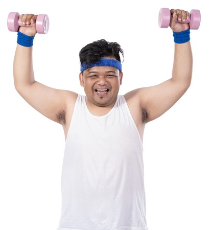 portrait of fat young toothy man doing exercise with arms lift dumbbells
