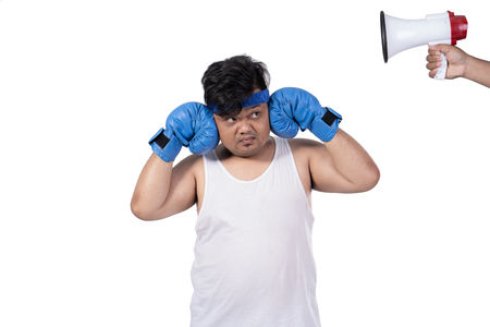 portrait of fat young man close his ears by hands with boxing gloves Stok Fotoğraf
