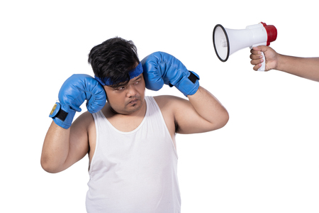 portrait of fat young man close his ears by hands and angry with boxing gloves
