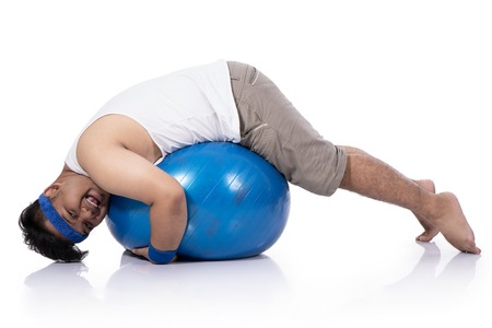 portrait of fat young man warms up pilates happily