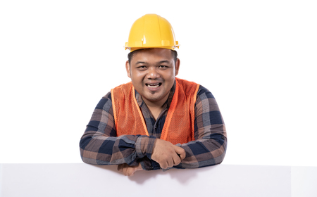portrait of happy handyman with helmet and uniform leaning on white board Stockfoto