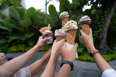 portrait of hands holding ice cream cone make a toast