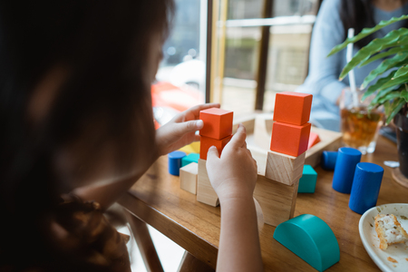 gesture of toddlers hand making a high tower from colorful wooden block Stockfoto