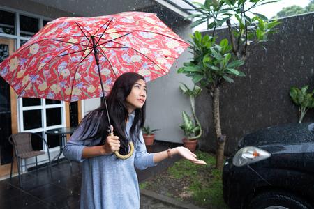 woman using umbrella while raining