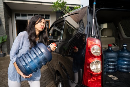 unhappy woman carrying a gallon of water