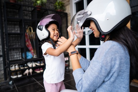 mom helped her daughter to put on helmet