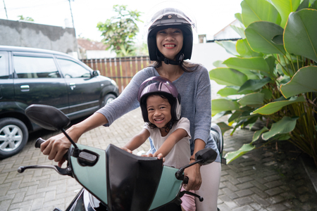 mom with her toddler child on motorbike