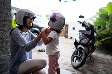 mother help her child to put on a helmet Stok Fotoğraf