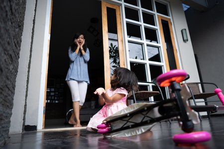 shocked mom looking at her daughter fell from scooter Stock Photo