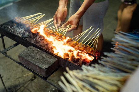 portrait of a seller cooking a skewers chicken meat with a grill