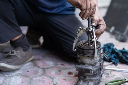 un meccanico con uno strumento di localizzazione dei cuscinetti rimuoverà una puleggia Archivio Fotografico