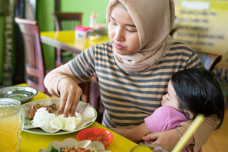 portrait of a mothers hijab carrying his daughter while eating