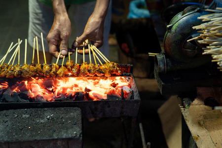 portrait of a cook hands grill a sate on the folding grill shelf Stock Photo - 115904869