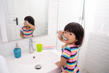 toddler independently brush her own teeth Stock Photo - 115904873