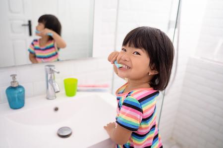 Niña asiática se cepilla los dientes y muestra sus dientes al cepillarse los dientes