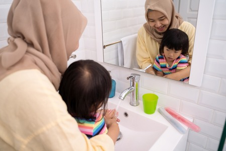 mom help her kid to wash her hands 版權商用圖片 - 115904877