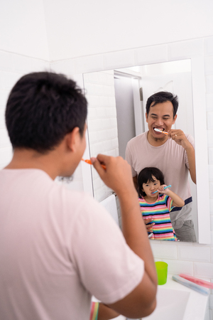 father and daughter brushing teeth together Stock Photo - 115904949