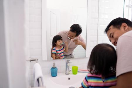 papá y niña se cepillan los dientes juntos