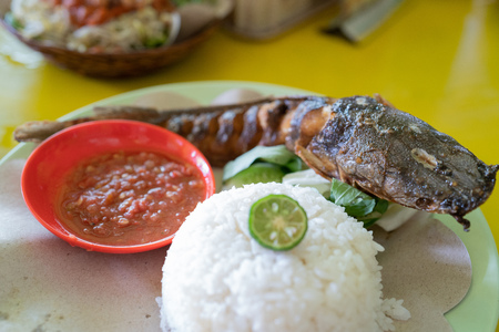 pecel ayam made from white rice, fried chicken with fresh vegetable and chili saos Stock Photo