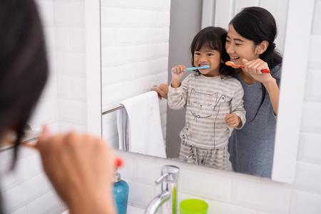 madre e hija cepillarse los dientes en el lavabo del baño Foto de archivo