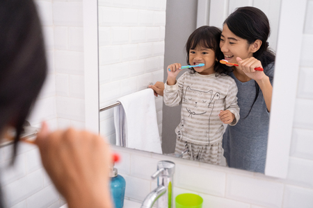 mother and daughter brushing teeth in the bathroom sink Stockfoto