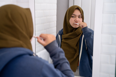 woman wearing hijab brush her teeth Banque d'images - 115904971