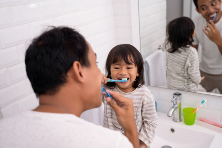 kid learn how to brush teeth with dad 版權商用圖片