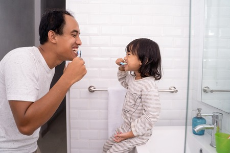 kid learn how to brush teeth with dad Stock Photo