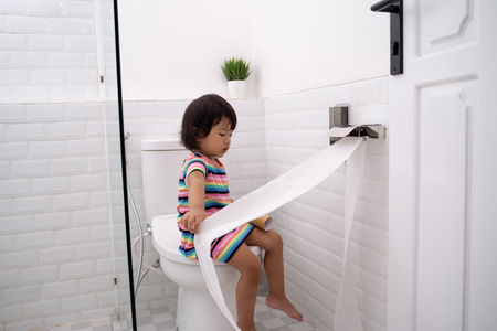 toddler pulling out toilet paper Stock Photo