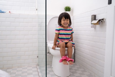 child sitting and learning how to use the toilet