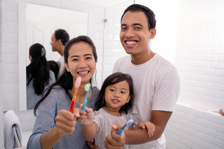 ather and mother with kid showing their tooth brush