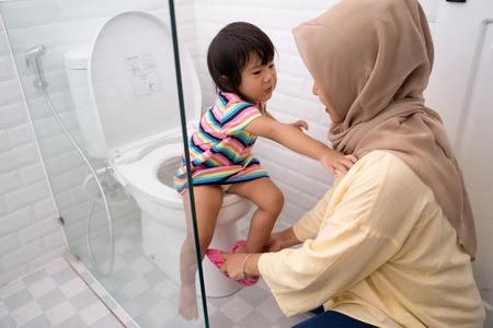 madre musulmana ayuda a su hijo a usar el baño