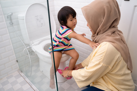muslim mother help her kid to use toilet Stock fotó