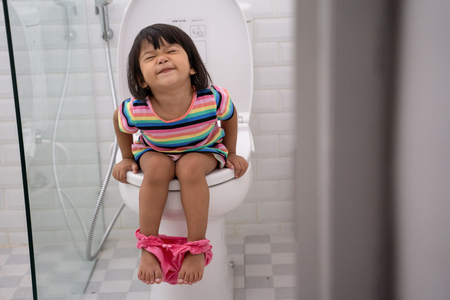 asian kid push it hard while sitting on toilet
