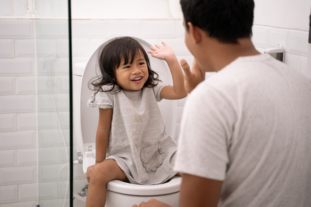 oddler high five with her dad while toilet traning 版權商用圖片