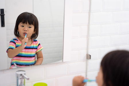 portrait of a very smart little girl brush her teeth is a routine activities Stock Photo - 115905346