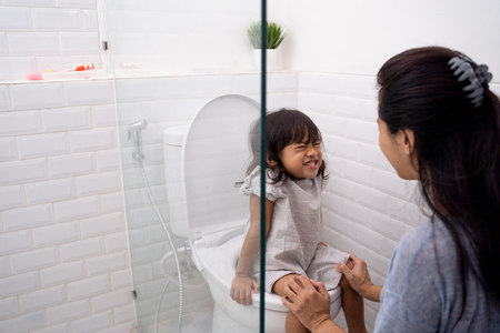 mother help her kid to use toilet