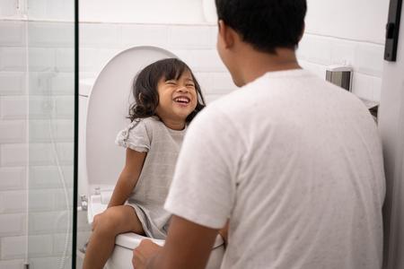 father teach her daughter toilet traning Reklamní fotografie