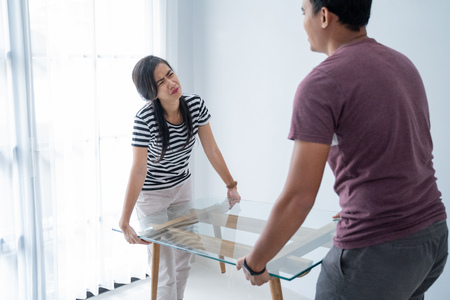 a new couple brings a table and his wife felt too heavy to lift furniture Imagens