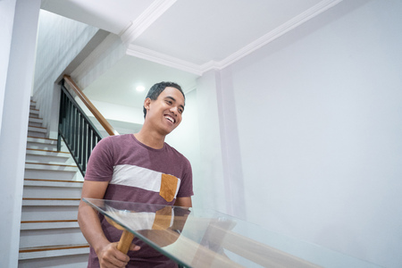 young asian man move a table upstair