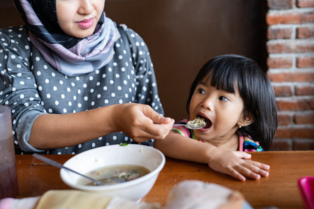muslim mother feed her daughter